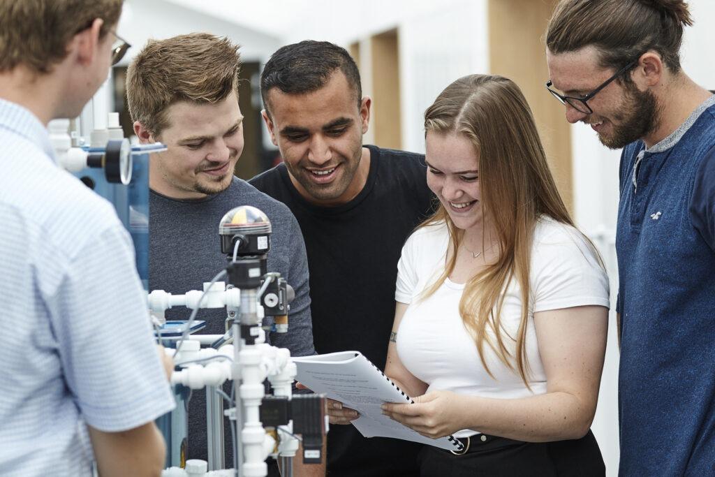 Gruppe af elever, der kigger på en opgave, de har lavet på Maskinmesteruddannelsen